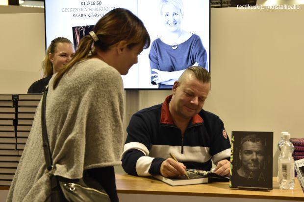Jari Sillanpää signeeraamassa kirjaansa. Jono oli pitkä ja työtä piti tehdä salamavalojen räiskeessä.