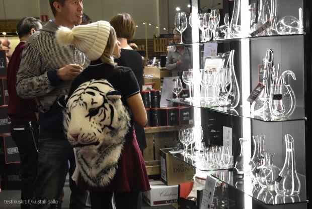 Riedelin arvostettuja viinilaseja ihailemassa olevan messuvieraan tiikerireppu ihastutti.